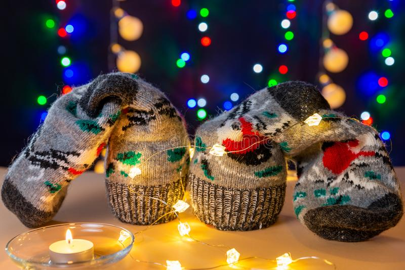 Present socks, lights and glowing candle are on the light table/background. There are different colors lights. Present socks, lights and glowing candle are on royalty free stock photography
