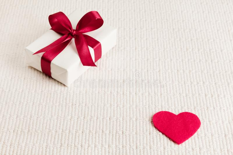 Present for Valentine`s day, Mother`s day or Wedding, wrapped in white paper, red bow next to a red heart on a light textile backg stock images