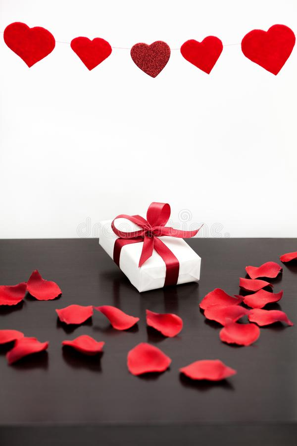 Present for Valentine`s day, Mother`s day or Wedding, wrapped in white paper, red bow and surrounded by red rose petals. royalty free stock photography