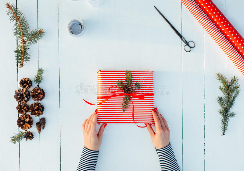 Present wrapped in red paper on a wooden background stock photo