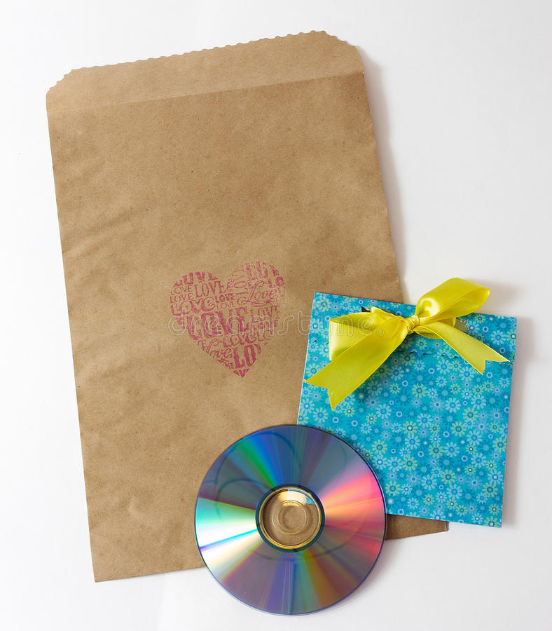 Present wrapper. For laser disk with craft paper envelope and cute handmade envelope on the white background royalty free stock images