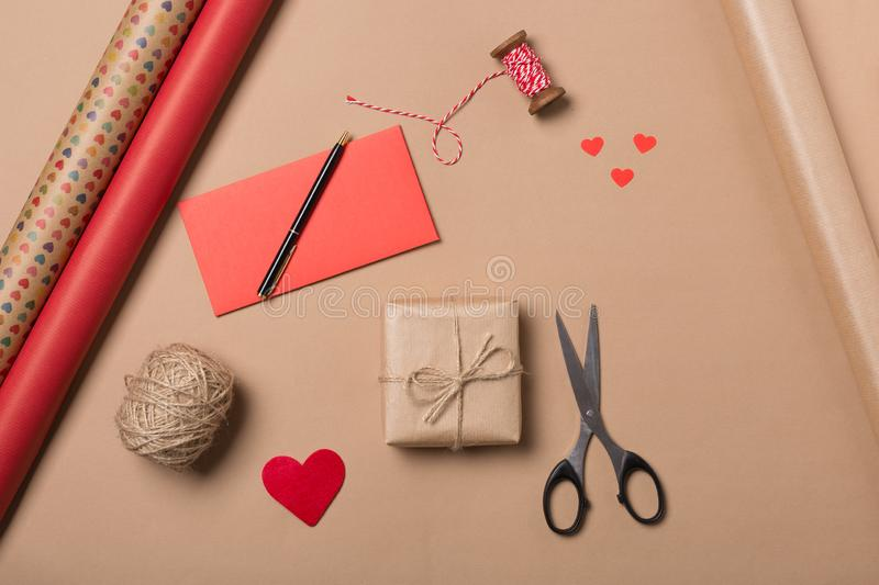 Present wrapping on beige table background. Gift in craft paper. Hearts. Creative Flat layout and top view composition stock photos