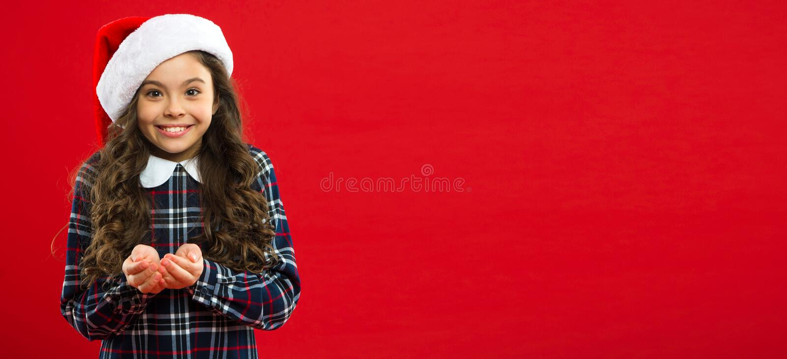 Present for Xmas. Childhood. New year party. Santa claus kid. Christmas shopping. Happy winter holidays. Small girl. Little girl child in santa red hat royalty free stock photo