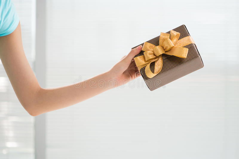 Present for you. Cropped image of a human hand holding a giftbox royalty free stock photos