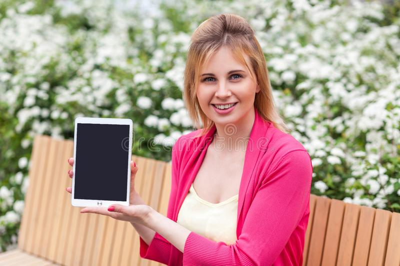 Present for you. Portrait of happy beautiful young businesswoman in casual style sitting in bench on park, showing tablet empty royalty free stock images