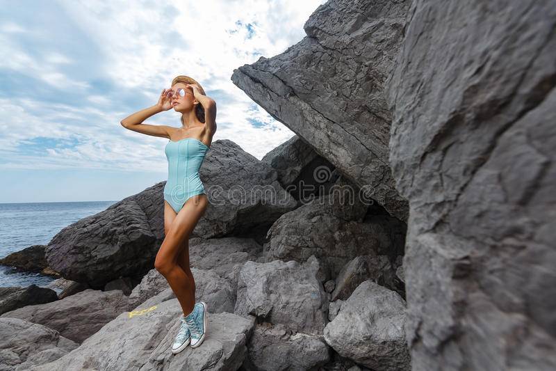 Presentación adolescente joven en piedras en la moda del mar fotografía de archivo
