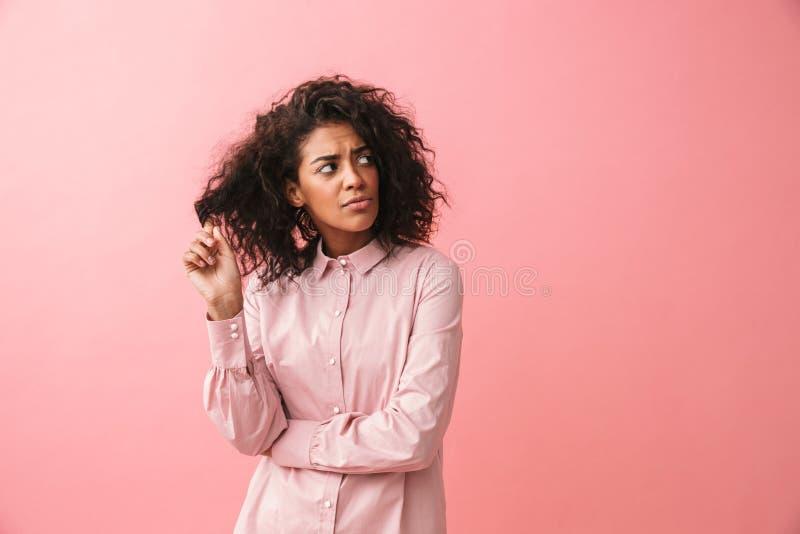 Presentación africana joven hermosa de pensamiento de la mujer aislada sobre el fondo rosado de la pared vestido en pijama imagen de archivo libre de regalías