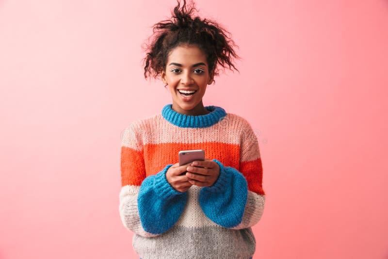 Presentación africana joven hermosa feliz de la mujer aislada sobre fondo rosado de la pared usando el teléfono móvil imagenes de archivo