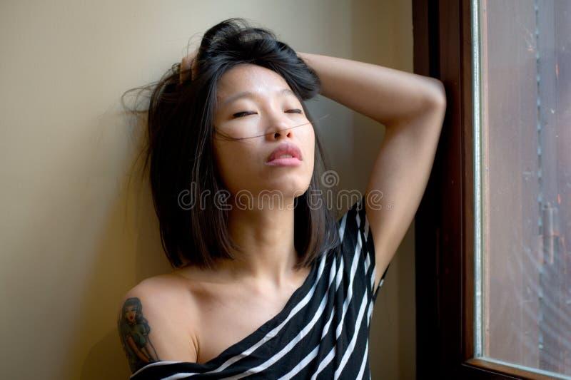 Presentación asiática sensual hermosa de la mujer pensativa en la ventana imágenes de archivo libres de regalías