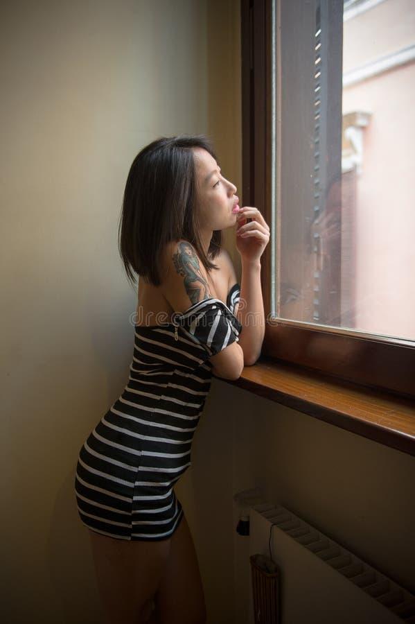 Presentación asiática sensual hermosa de la mujer pensativa en la ventana imagenes de archivo