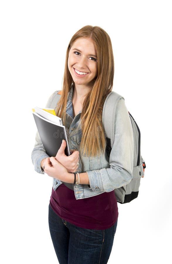 Presentación de la mochila y de los libros de la muchacha hermosa joven del estudiante universitario que lleva feliz y confiada e fotografía de archivo libre de regalías