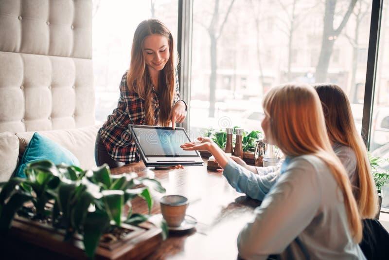 Presentación de mercancías en el ordenador portátil, encontrándose en café foto de archivo libre de regalías