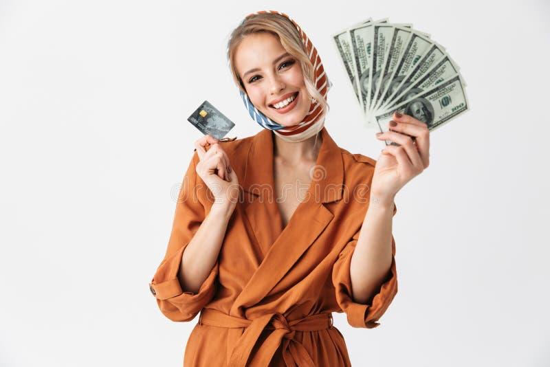 Presentación de seda de la bufanda de la mujer que lleva bonita rubia joven alegre aislada sobre el fondo blanco de la pared que  foto de archivo