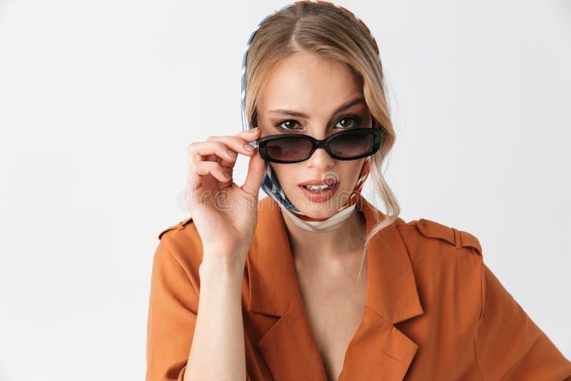 Presentación de seda de la bufanda y de las gafas de sol de la mujer que lleva bonita rubia joven aislada sobre el fondo blanco d imagen de archivo libre de regalías