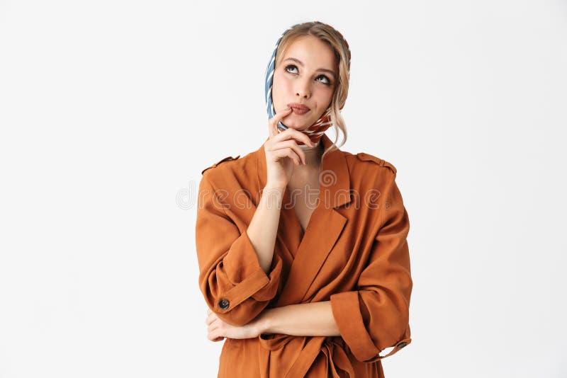 Presentación de seda de pensamiento hermosa de la bufanda de la mujer que lleva bonita rubia joven pensativa aislada sobre el fon fotografía de archivo libre de regalías