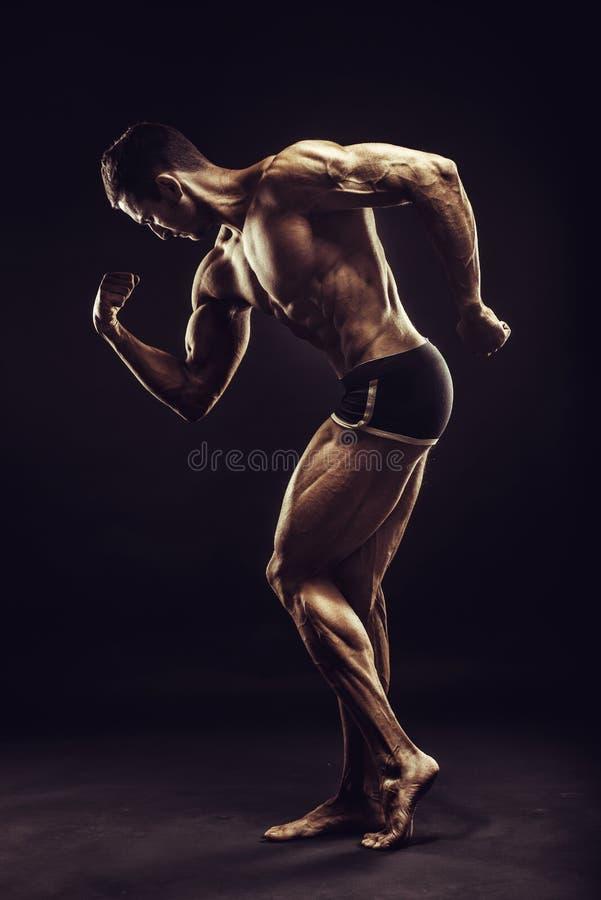 Presentación del hombre del culturista, mostrando el ABS perfecto, houlders, bíceps, tríceps, pecho imagenes de archivo