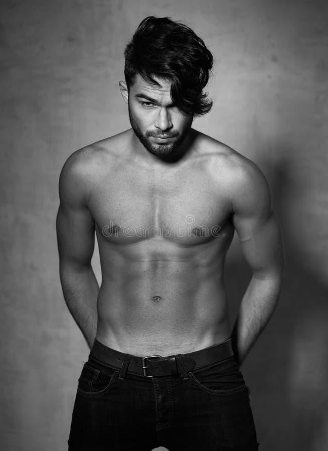 Presentación desnuda superior de la moda del modelo atractivo del hombre dramática contra la pared del grunge imagen de archivo libre de regalías