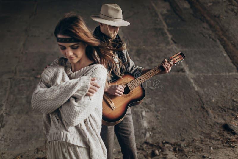 Presentación elegante de los pares del inconformista hombre en el sombrero que toca la guitarra para el suyo imagen de archivo libre de regalías