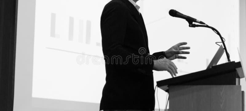 Presentación empresarial que está a cargo del presentador. Seminario corporativo con expertos que presentan a las personas. Homb foto de archivo