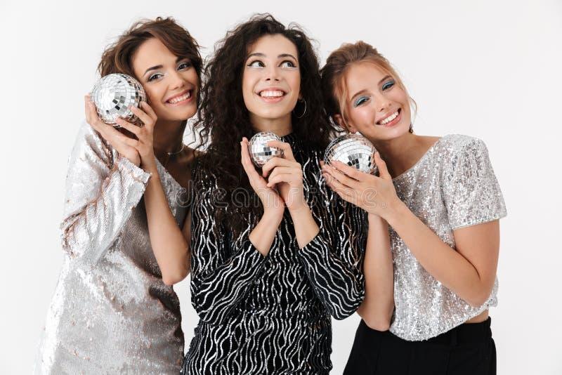 Presentación feliz joven de los amigos de las mujeres aislada sobre el fondo blanco de la pared En un partido imágenes de archivo libres de regalías