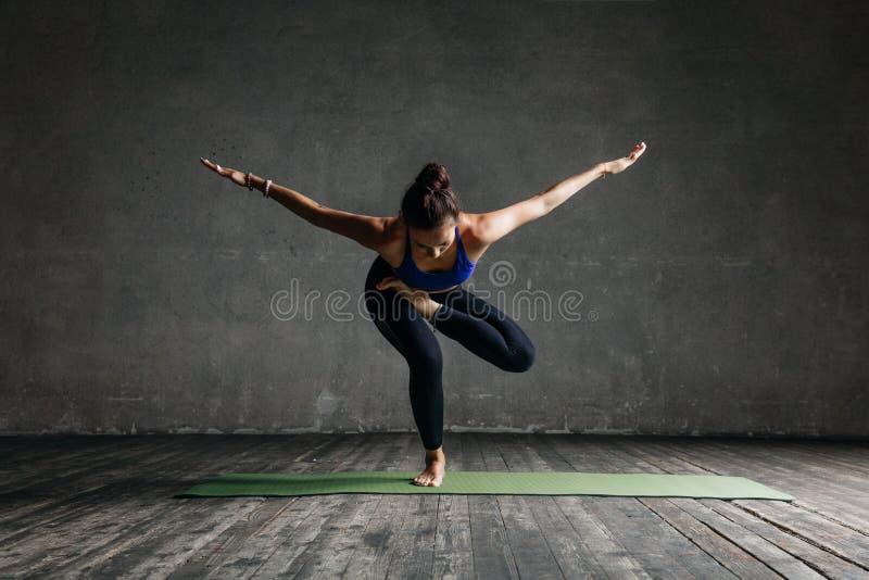 Presentación femenina de la yoga hermosa joven en estudio foto de archivo