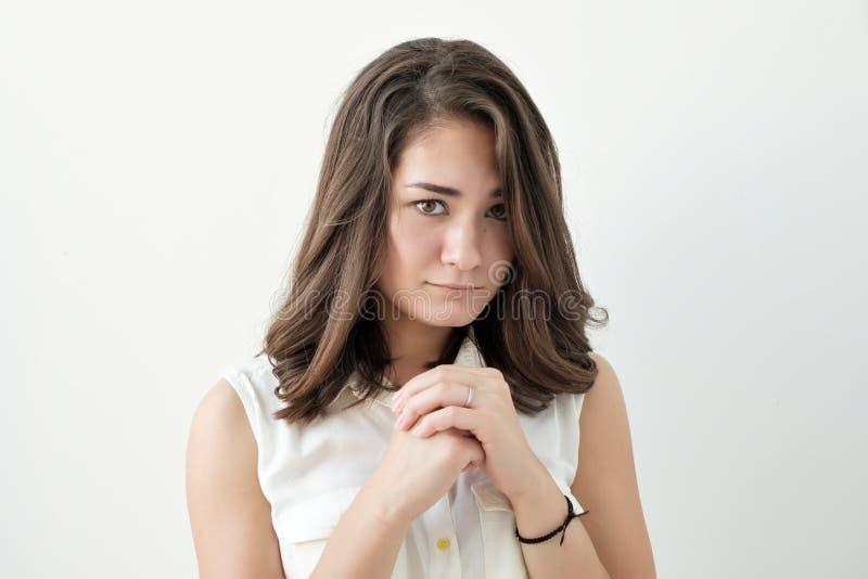 Presentación femenina joven confusa aislada en la pared blanca imagen de archivo