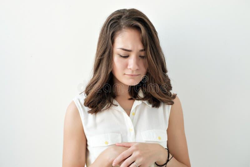 Presentación femenina joven confusa aislada en la pared blanca foto de archivo