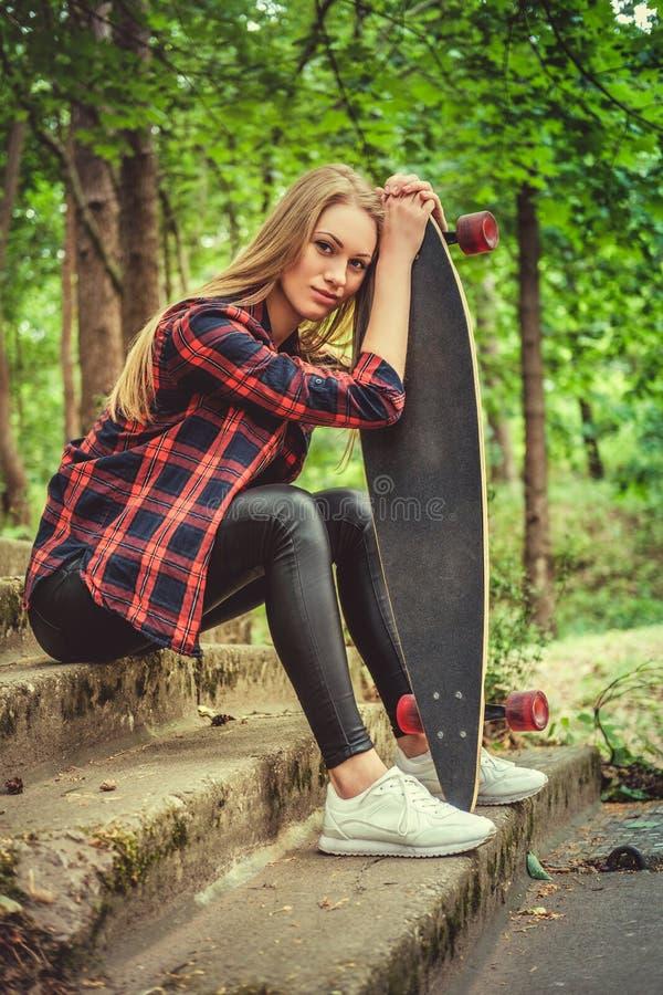 Presentación femenina rubia casual con longboard en las escaleras foto de archivo