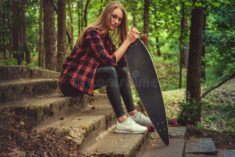 Presentación femenina rubia casual con longboard en las escaleras imágenes de archivo libres de regalías