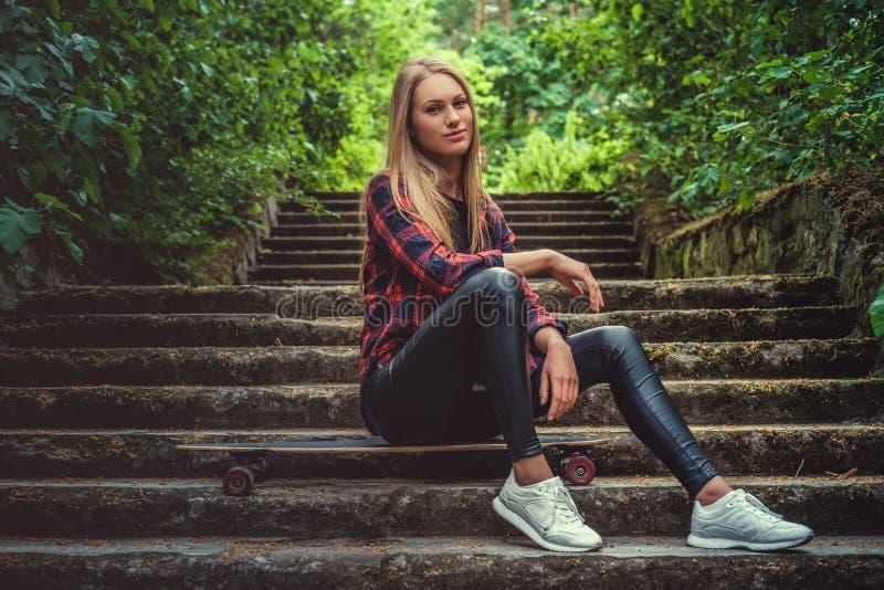 Presentación femenina rubia casual con longboard en las escaleras imagenes de archivo