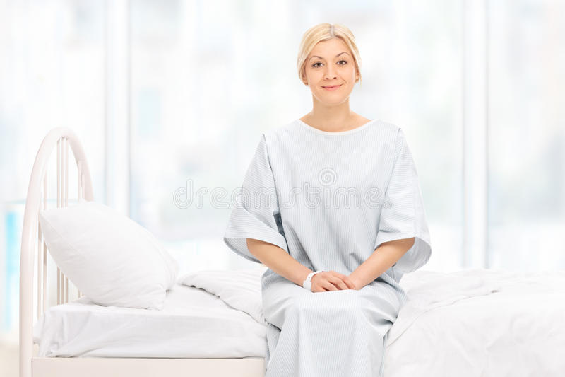 Presentación femenina rubia del paciente asentada en una cama de hospital imagen de archivo libre de regalías