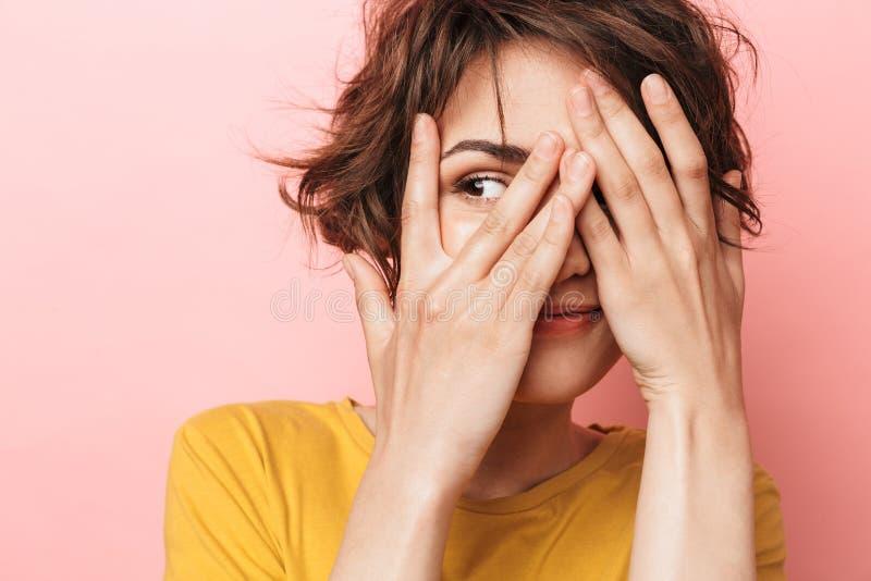 Presentación hermosa divertida joven de la mujer aislada sobre cara rosada de la cubierta del fondo de la pared imagenes de archivo