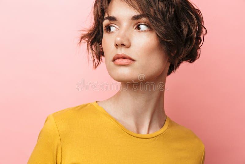 Presentación hermosa joven de la mujer aislada sobre fondo rosado de la pared foto de archivo