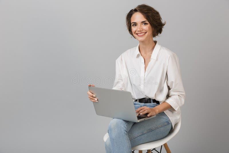 Presentación joven de la mujer de negocios aislada sobre el fondo gris de la pared que se sienta en taburete usando el ordenador  foto de archivo libre de regalías