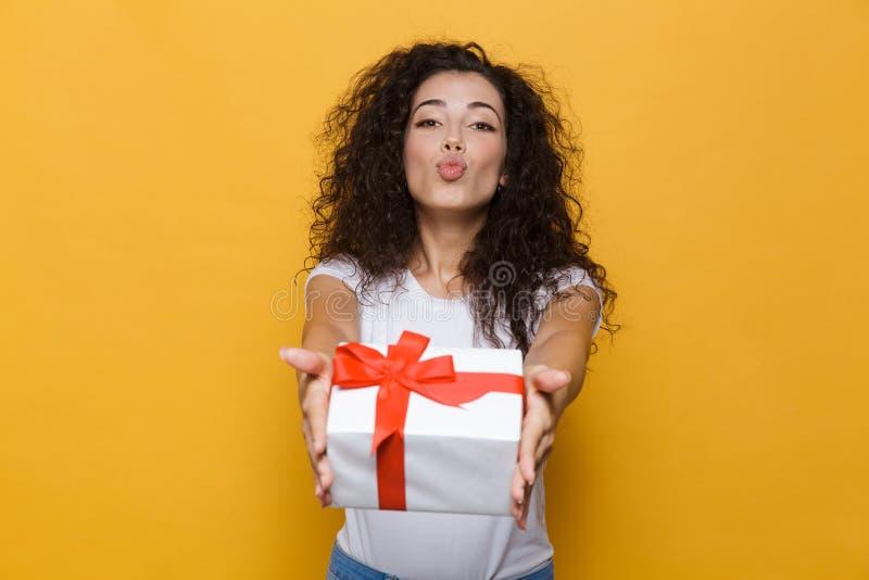 Presentación linda feliz de la mujer joven aislada sobre presente amarillo de la caja de regalo de la tenencia del fondo imágenes de archivo libres de regalías