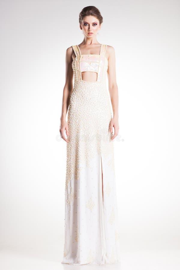 Presentación modelo de la mujer hermosa en vestido blanco elegante de la perla foto de archivo libre de regalías