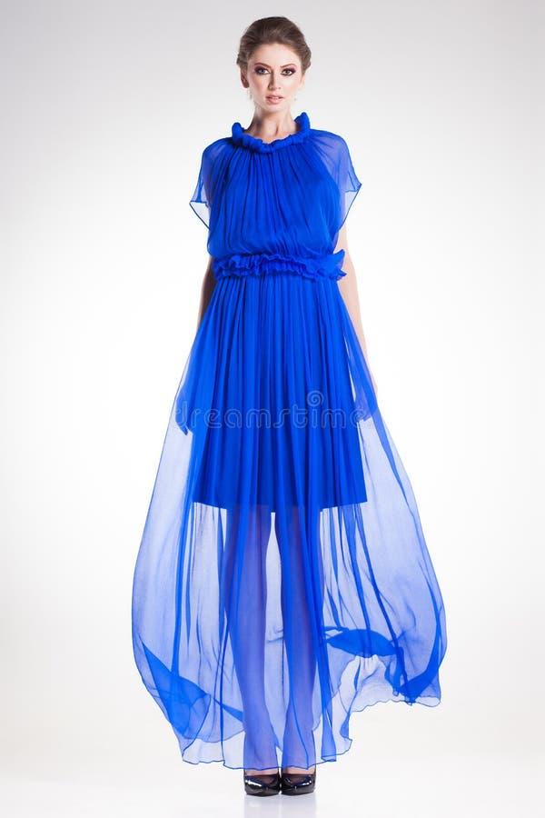 Presentación modelo de la mujer hermosa en vestido de seda azul elegante largo imagenes de archivo