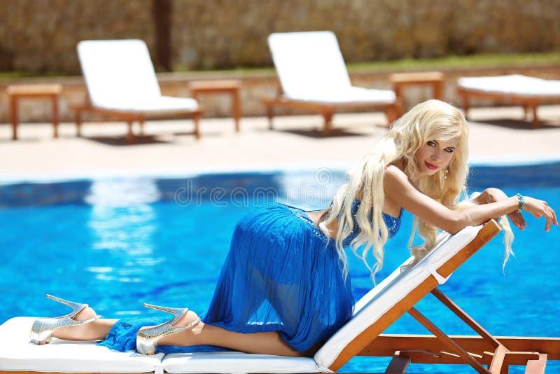 Presentación modelo de la mujer rubia de la moda de la belleza en vestido largo azul en el de fotos de archivo