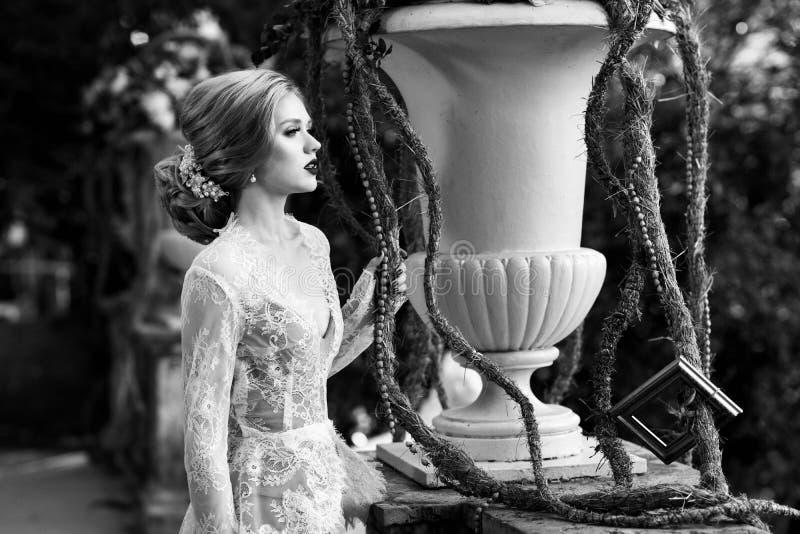 Presentación modelo femenina al lado de la barandilla de piedra y del vaso grande de la flor imagenes de archivo