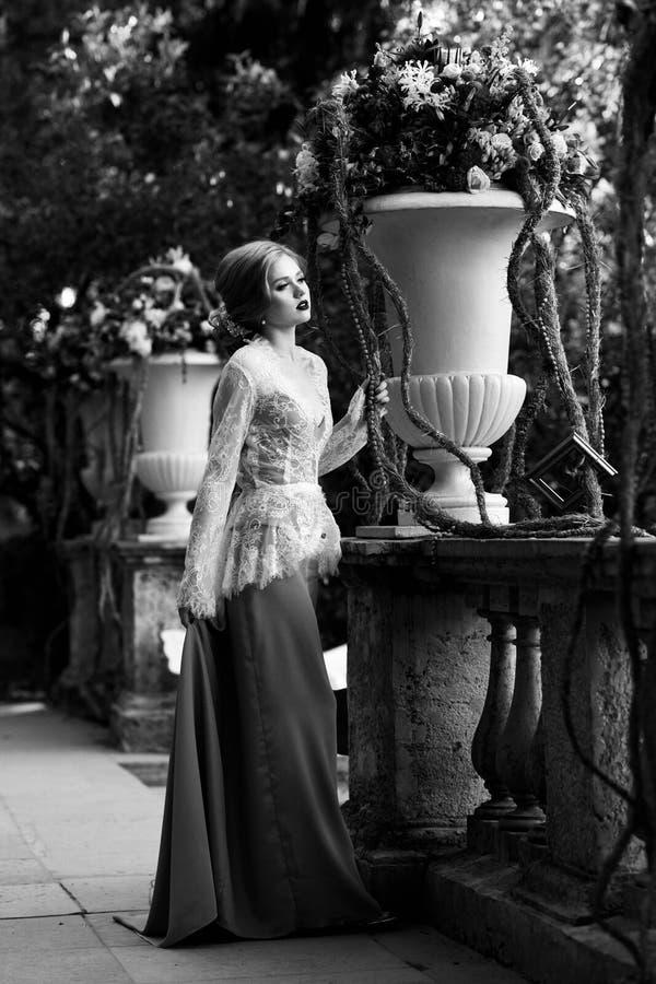Presentación modelo femenina al lado de la barandilla de piedra y del vaso grande de la flor foto de archivo