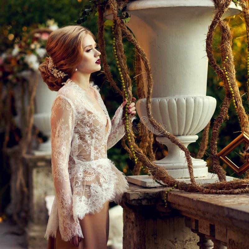 Presentación modelo femenina al lado de la barandilla de piedra y del vaso grande de la flor fotografía de archivo libre de regalías