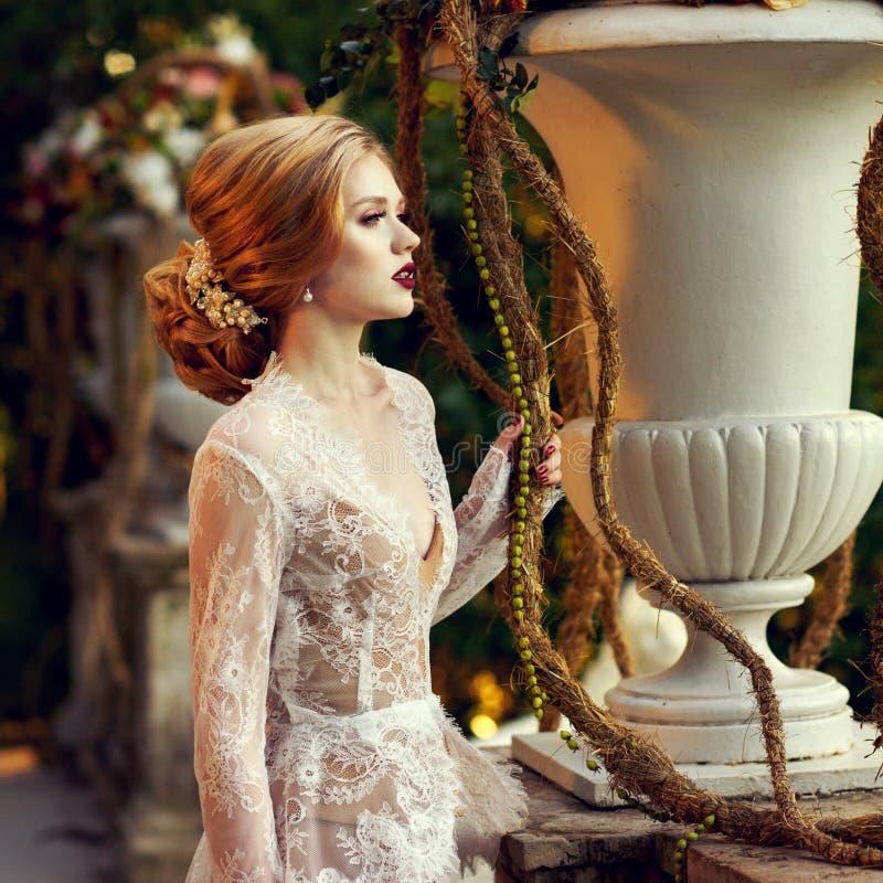 Presentación modelo femenina al lado de la barandilla de piedra y del vaso grande de la flor foto de archivo libre de regalías