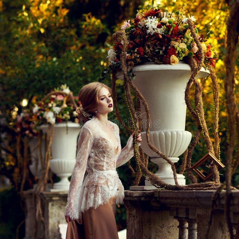 Presentación modelo femenina al lado de la barandilla de piedra y del vaso grande de la flor fotografía de archivo