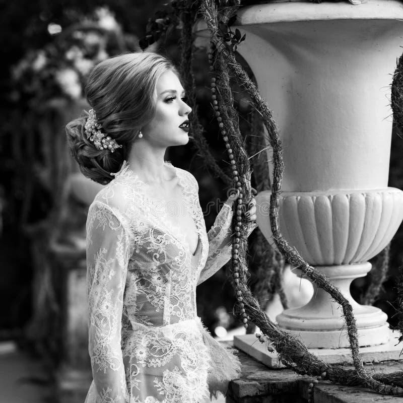 Presentación modelo femenina al lado de la barandilla de piedra y del vaso grande de la flor imágenes de archivo libres de regalías