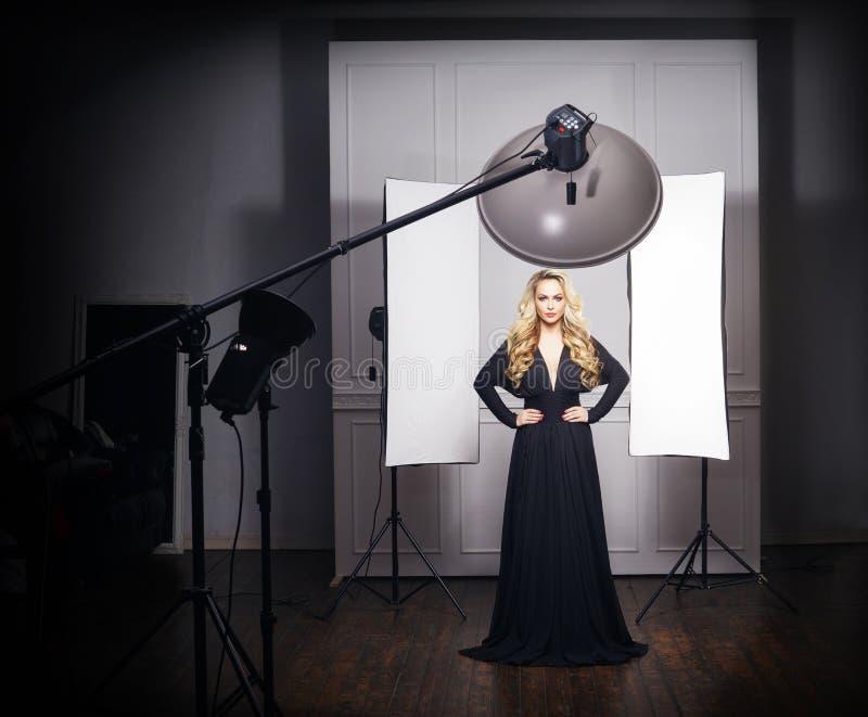 Presentación modelo hermosa en vestido negro en estudio de la foto imagenes de archivo