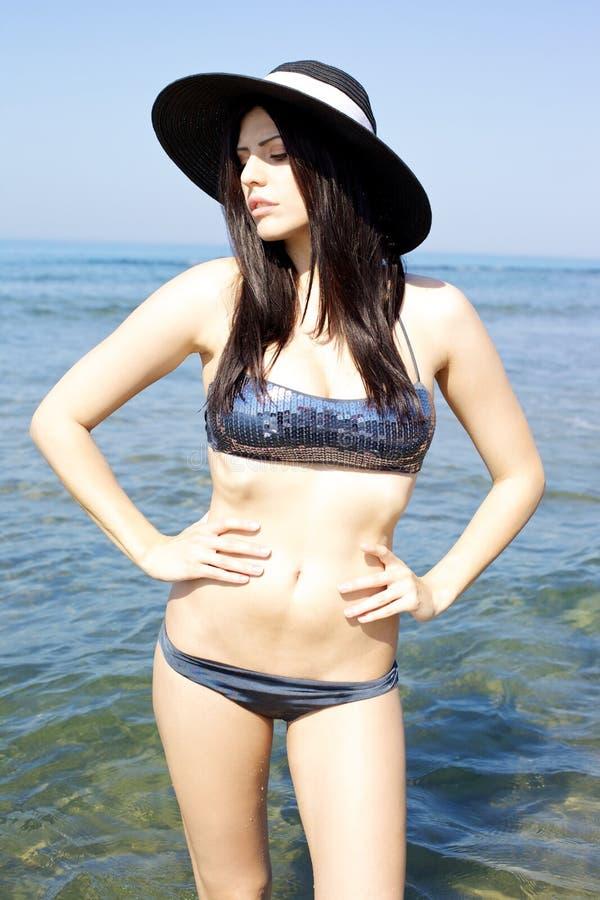 Presentación modelo seria en el mar con el sombrero negro foto de archivo