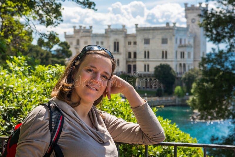 Presentación morena atractiva delante del castillo de Miramare fotos de archivo