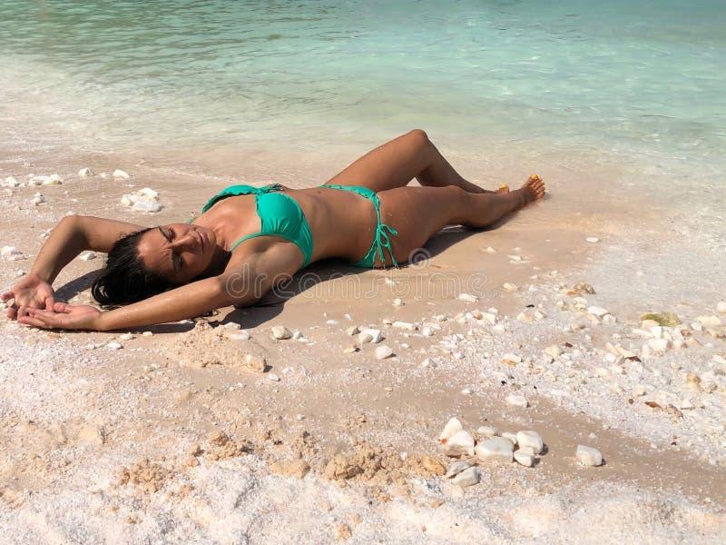 Presentación morena atractiva en la playa imagen de archivo