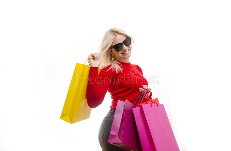 Presentación rubia atractiva en estudio con los bolsos de compras fotografía de archivo libre de regalías