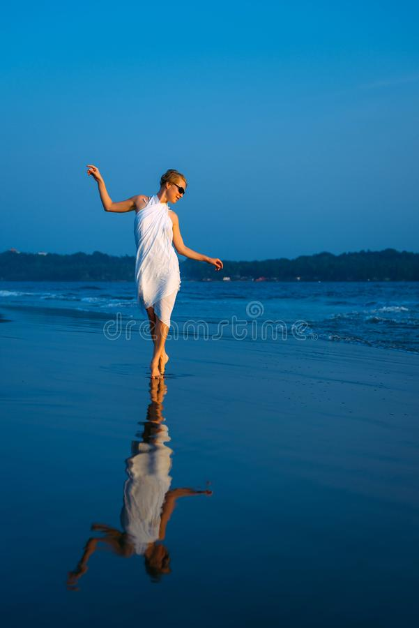 Presentación rubia hermosa y atractiva feliz joven contra el mar azul en el vestido y las gafas de sol blancos Muchacha elegante  foto de archivo libre de regalías